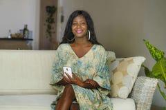 Jeune belle et heureuse femme afro-américaine noire élégante posant au divan de sofa de salon en son appartement moderne utilisan images libres de droits