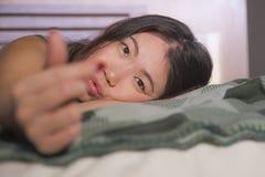 Jeune belle et heureuse femme chinoise asiatique se situant dans la chambre à coucher de lit à la maison souriant amour faisant d photographie stock libre de droits