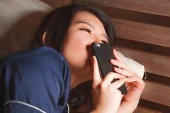 Jeune belle et heureuse femme coréenne asiatique dans des pyjamas embrassant le service de mini-messages de téléphone portable av photos stock