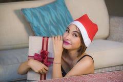 Jeune belle et heureuse fille dans le chapeau de Santa tenant la boîte de cadeau de Noël avec le ruban souriant à la maison divan images libres de droits