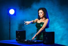 Jeune, belle et sexy fille du DJ jouant la musique sur une partie de disco dans une boîte de nuit images libres de droits