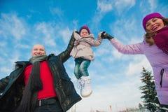 Jeune belle famille dans l'amusement lumineux d'hiver de vêtements sautant et fonctionnant, neige, mode de vie, vacances d'hiver Photos libres de droits