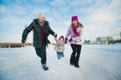 Jeune belle famille dans l'amusement lumineux d'hiver de vêtements sautant et fonctionnant, neige, mode de vie, vacances d'hiver Photo stock