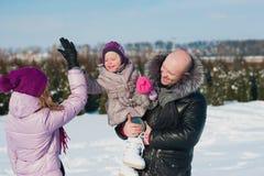 Jeune belle famille dans l'amusement lumineux d'hiver de vêtements sautant et fonctionnant, neige, mode de vie, vacances d'hiver Image stock