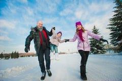 Jeune belle famille dans l'amusement lumineux d'hiver de vêtements sautant et fonctionnant, neige, mode de vie, vacances d'hiver Images libres de droits