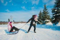 Jeune belle famille dans l'amusement lumineux d'hiver de vêtements sledding, neige, mode de vie, vacances d'hiver Photo stock