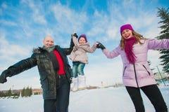Jeune belle famille dans l'amusement lumineux d'hiver de vêtements sledding, neige, mode de vie, vacances d'hiver Photographie stock libre de droits