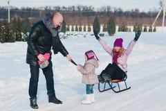 Jeune belle famille dans l'amusement lumineux d'hiver de vêtements sledding, neige, mode de vie, vacances d'hiver Photographie stock