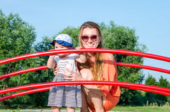 Jeune belle famille heureuse de bébé de mère et de fille jouant sur l'oscillation, et tour dans le sourire de parc d'attractions Photos stock