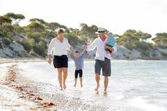Jeune belle famille heureuse marchant ensemble sur la plage appréciant des vacances d'été Photographie stock