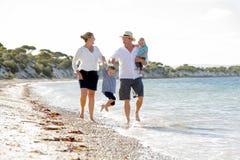 Jeune belle famille heureuse marchant ensemble sur la plage appréciant des vacances d'été Photo libre de droits