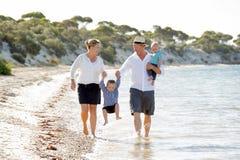Jeune belle famille heureuse marchant ensemble sur la plage appréciant des vacances d'été Image stock