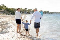Jeune belle famille heureuse marchant ensemble sur la plage appréciant des vacances d'été Images libres de droits