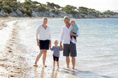 Jeune belle famille heureuse marchant ensemble sur la plage appréciant des vacances d'été Photographie stock libre de droits