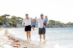 Jeune belle famille heureuse marchant ensemble sur la plage appréciant des vacances d'été Images stock