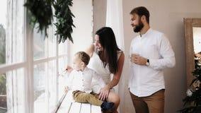 Jeune belle famille s'asseyant ensemble par la fenêtre décorée de la guirlande de Noël Parents affectueux s'embrassant dedans banque de vidéos