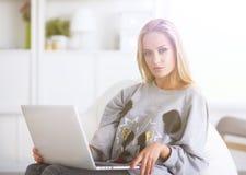 Jeune belle femme à l'aide d'un ordinateur portable à la maison image libre de droits