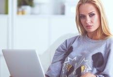 Jeune belle femme à l'aide d'un ordinateur portable à la maison photographie stock
