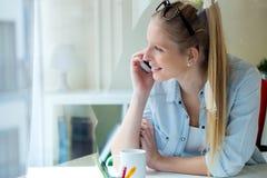 Jeune belle femme à l'aide de son téléphone portable à la maison Photographie stock libre de droits