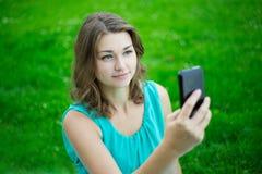 Jeune belle femme à l'aide du téléphone intelligent dans le parc Image libre de droits