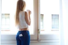 Jeune belle femme à la maison avec le téléphone portable dans la poche arrière Images libres de droits