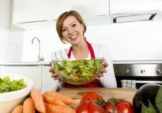 Jeune belle femme à la maison de cuisinier à la cuisine moderne préparant le sourire végétal de saladier heureux photo stock