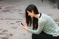 Jeune belle femme écoutant la musique avec le téléphone dedans dehors photographie stock
