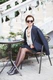 Jeune belle femme élégante dans des lunettes de soleil se reposant dans un café potable extérieur de café images libres de droits
