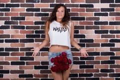 Jeune belle femme étonnée avec des roses entre ses jambes Image stock