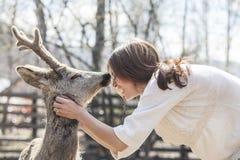Jeune belle femme étreignant les cerfs communs d'OEUFS DE POISSON animaux au soleil Photos libres de droits