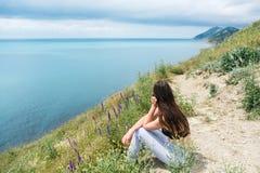 Jeune belle femme 25-30 ans se reposant sur la montagne et les regards en mer, vue de côté Photos stock