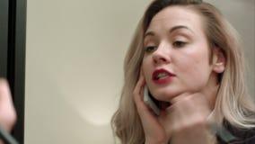 Jeune belle femme appliquant le maquillage sur le visage avec la brosse, ayant l'appel téléphonique, étant en retard banque de vidéos