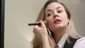 Jeune belle femme appliquant le maquillage sur le visage avec la brosse, ayant l'appel téléphonique, étant en retard Image libre de droits