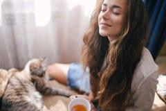 Jeune belle femme appréciant son thé de matin images stock
