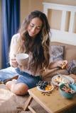 Jeune belle femme appréciant son thé de matin photo stock