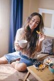 Jeune belle femme appréciant son thé de matin image stock