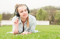 Jeune belle femme appréciant la musique dehors sur des écouteurs Photographie stock libre de droits
