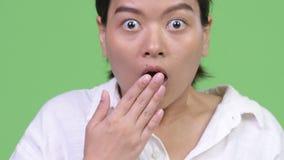 Jeune belle femme asiatique semblant choquée tout en couvrant la bouche