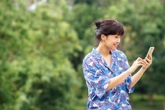Jeune belle femme asiatique souriant tout en lisant son smartphone photographie stock libre de droits