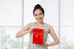Jeune belle femme asiatique tenant le boîte-cadeau rouge images stock