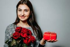 Jeune belle femme attirante avec les roses rouges et le boîte-cadeau, Co Image stock