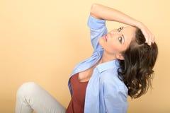Jeune belle femme attirante s'asseyant sur le plancher Image stock