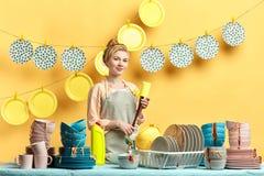 Jeune belle femme au foyer de sourire dans l'éponge grise de participation de tablier photos libres de droits