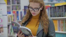 Jeune belle femme aux cheveux roux brillants dans les lunettes, jolie fille dans les lunettes Lire à la bibliothèque du livre Uni banque de vidéos
