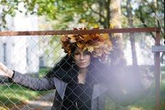 Jeune belle femme avec des feuilles d'automne de couronne Image stock