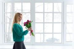 Jeune belle femme avec des tulipes par la fenêtre, le 8 mars, copyspace Image libre de droits