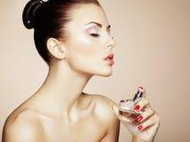 Jeune belle femme avec la bouteille de parfum. Maquillage parfait Images stock