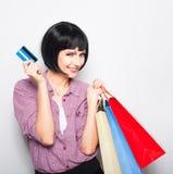 Jeune belle femme avec la carte de crédit et les paniers Photos libres de droits