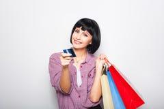 Jeune belle femme avec la carte de crédit et les paniers Images stock