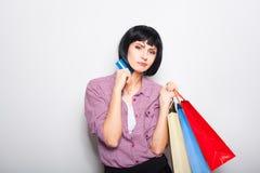 Jeune belle femme avec la carte de crédit et les paniers Photos stock